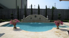 Classic-roman-design-pool-with-raised-stucco-wall-bronze-water-spouts-travertine-decking-diamond-brite-plaster