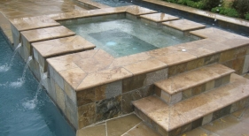 Raised-spa-with-bull-nosed-noche-travertine-coping-white-gold-quartzite-mosaic-tile-franche-gray-plaster-lap-pool