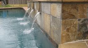Raised-spa-with-three-natural-stone-spouts-bull-nosed-travertine-coping-quartzite-wall-tile-diamond-brite-plaster