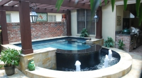 raised-concrete-pool-spa-with-granite-spillover-basin-glass-mosaic-water-wall-brass-cascade-fountains