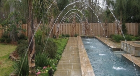 raised-lap-pool-with-dark-bull-nosed-travertine-coping-french-gray-plaster-white-gold-quartzite-waterline-tile-colored-laminar-jets