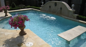 small-pool-with-granite-pool-table-bronze-emitters-raised-stucco-wall-travertine-coping-and-deck