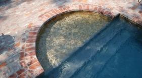 tanning-ledge-with-quartzite-mosaic-overlay-diamond-brite-french-gray-plaster-antique-brick-coping