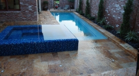 concrete-reflective-blue-tiled-spa-travertine-covered-tanning-ledge-pavers