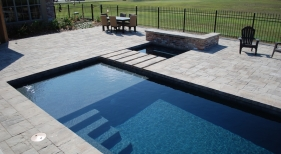 contemporary-gunite-pool-with-tanning-ledge-dark-diamond-brite-plaster-step-bridge-spa-raied-wall-brick-pavers