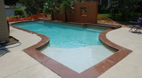 gunite-pool-with-colored-cast-concrete-coping-baja-shelf-diamond-brite-pearl-plaster-raised-wall