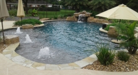 Freeform, natural pool with bubblers, tanning ledge, loveseat grotto, bookend rico rock boulders and pool landscaping