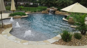 Freeform-natural-pool-with-bubblers-tanning-ledge-loveseat-grotto-bookend-rico-rock-boulders-and-pool-landscaping
