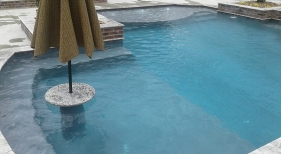 Geometric-pool-with-tanning-ledge-geometric-spa-with-perimeter-overflow-cocktail-table-with-umbrella-_-copper-scuppers1
