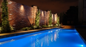 gunite-pool-with-led-pool-lights-gold-travertine-coping-antique-brick-wall-diamond-brite-blue-quartz-plaster