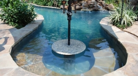 natural-gunite-lagoon-pool-with-rock-waterfall-and-pool-granite-cocktail-table-with-umbrella-holder