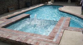 pool-and-spa-combo-with-antique-brick-tile-accents-spa-fountain-diamond-brite-blue-quartz-plaster