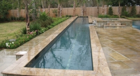raised-lap-pool-with-noche-Mexican-travertine-coping-quartzite-lap-line-french-gray-diamond-brite-plaster-natural-stone-covered-spa-spouts