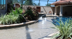 custom-gunite-pool-tanning-ledge-with-pebble-plaster-finish-bubblers-laminar-jets-tropical-landscaping