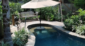 freeform-gunite-pool-with-cocktail-table-flagstone-bench-flagstone-coping-umbrella-holder