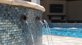 raised-gunite-spa-glass-mosaic-tile-copper-spillover-spouts-sunken-bar-travertine-stools-artistic-paver-coping
