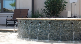 raised-gunite-spa-with-copper-spillover-spouts-glass-mosaic-tile-artistic-paver-coping-tanning-ledge-with-pebble-finish