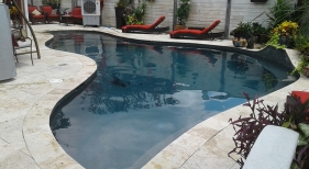 Custom-modern-pool-with-tanning-ledge-deck-jets-sheer-descents-waterfall-travertine-decking