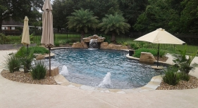 Freeform-natural-pool-with-bubblers-tanning-ledge-loveseat-grotto-bookend-rico-rock-boulders-and-pool-landscaping-3