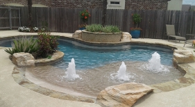 Freeform-pool-flagstone-coping-beach-entry-rico-rock-boulders-bubblers-and-raised-planter-box-2