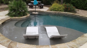 Freeform-pool-with-tanning-ledge-ledge-loungers-rock-waterfall-cocktail-table-with-umbrella-2