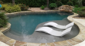 Freeform pool with tanning ledge, ledge loungers, rock waterfall, cocktail table with umbrella