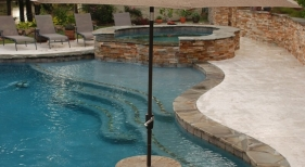 freeform-gunite-pool-with-negative-edge-granite-cocktail-table-bench-tanning-ledge-raised-spa-flagstone-ledger-stone (1)