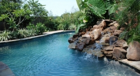 natural-shape-pool-with-flagstone-coping-rock-waterfall-diamond-brite-french-gray-plaster-finish