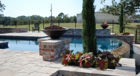 negative-edge-concrete-pool-with-belgard-pavers-grand-effects-fire-water-bowls-raised-antique-brick-walls