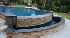 vanishing-edge-concrete-pool-with-a-ledger-stone-water-wall-bluestone-coping-shellstone-pavers